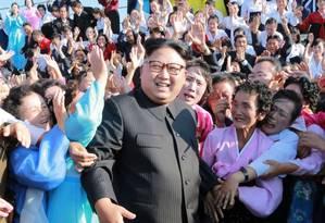 Imagem da agência estatal mostra Kim Jong-un posando para fotos ao lado de norte-coreanos Foto: STR / AFP