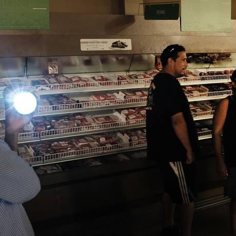 Pessoas fazem compras auxiliadas por lanternas na Flórida Foto: SPENCER PLATT / AFP