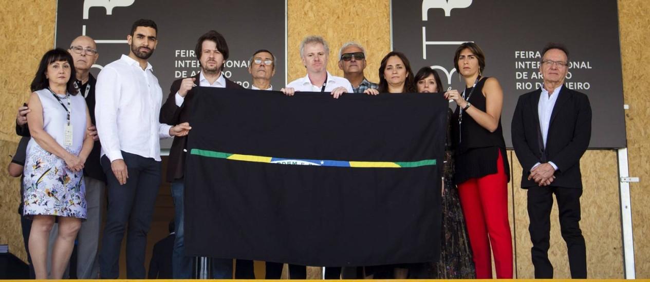 Entre galeristas e curadores, Marcio Botner (centro) segura obra de Alexandre Vogler Foto: Leo Martins / Agência O Globo