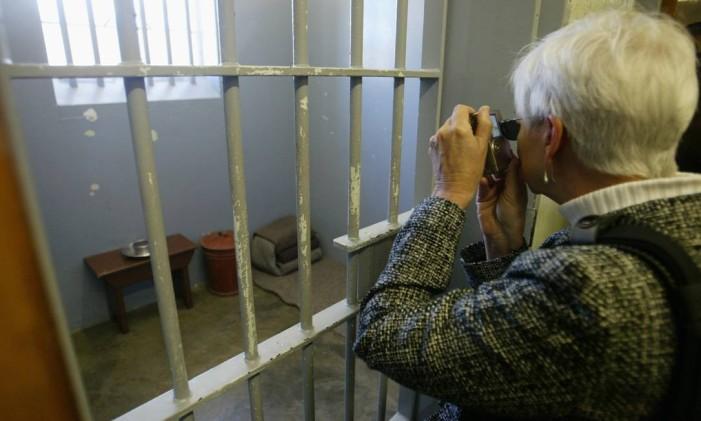 Visitante em frente à cela onde Nelson Mandela esteve preso em Robben Island, na África do Sul Foto: Márcia Foletto / Agência O Globo/Arquivo