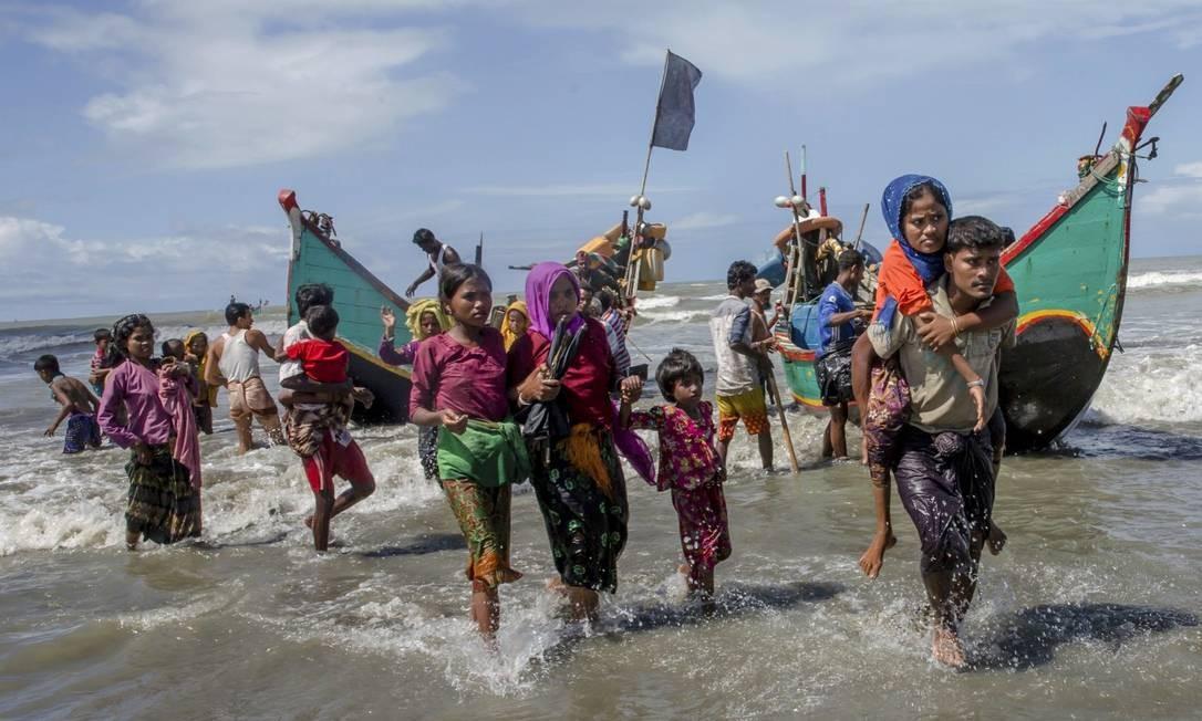 Muçulmanos rohingya deixam embarcação precária após chegar de Mianmar a Bangladesh, na fuga da perseguição Foto: Dar Yasin / AP