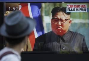Homem assiste programa com imagem do líder norte-coreano, Kim Jong-un Foto: Eugene Hoshiko / AP