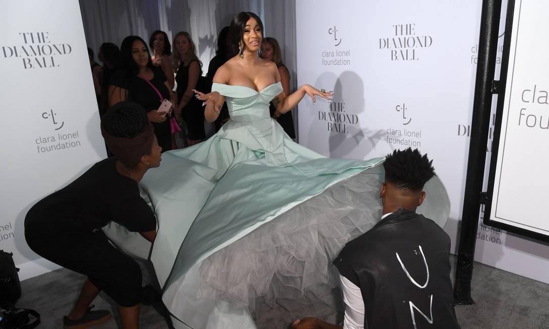 """Isso é que dá querer usar um vestido gigante. A rapper Cardi B, uma das convidadas do Diamond Ball, baile beneficente da ONG de Rihanna, que aconteceu na noite da última quinta-feira, precisou da ajuda de duas pessoas para caminhar com """"caminhão em forma de roupa"""" Foto: ANGELA WEISS / AFP"""
