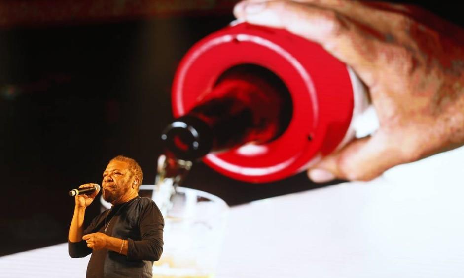 Martinho da Vila com imagem de uma bela garrafa de cerveja ao fundo Foto: Agência O Globo