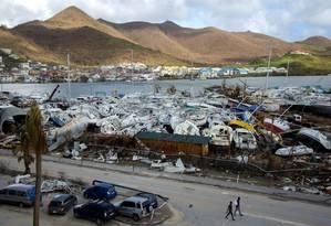 Pessoas caminham próximo a botes devastados em Marigot, na parte francesa da ilha de St. Martin Foto: HELENE VALENZUELA / AFP