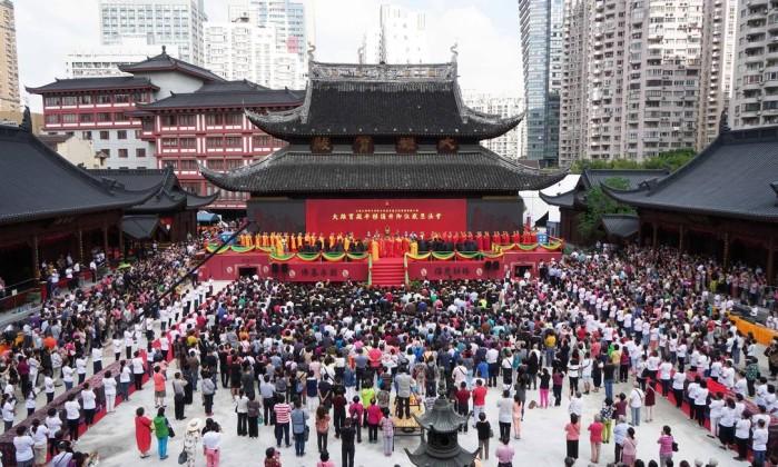 Foto tirada neste domingo mostra visitantes participando da cerimônia de conclusão do deslocamento do salão principal do templo de Yufo, também conhecido como o templo do Buda de Jade, em Xangai - STR / AFP