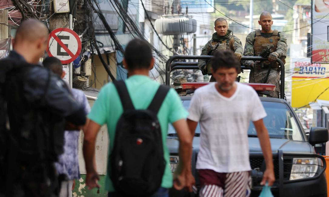 Moradores da Rocinha saem para trabalhar enquanto carro do Bope percorre via da favela Foto: Fabiano Rocha / Agência O Globo