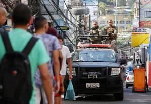 Moradores passam por carro da Polícia Militar em operação na Favela da Rocinha Foto: Fabiano Rocha / Agência O Globo