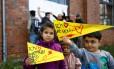 Crianças sírias refugiadas seguram cartazes de apoio a primeira ministra alemã, Angela Merkel, em Wismar, na Alemanha. Foto: AXEL SCHMIDT / REUTERS