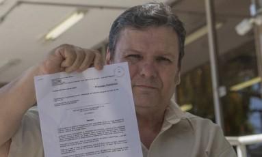 Ribeiro mostra decisão que obriga o estado a ceder remédio ao filho Foto: Agência O Globo / Analice Paron