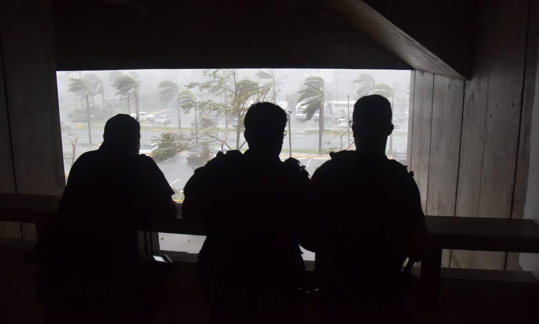 Pessoas olham a passagem do furacão Maria em um estacionamento em San Juan, Porto Rico. Segundo o Centro Nacional de Furacões americano, o fenômeno tem ventos de 250 km/h Foto: HECTOR RETAMAL / AFP
