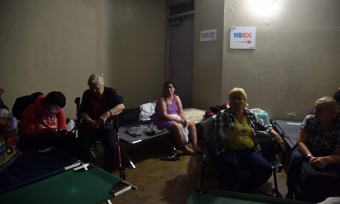 Pessoas se abrigam em San Juan durante a passagem do furacão Maria. Apesar de ter enfraquecido, Maria permanece representando um extremo perigo para a região Foto: HECTOR RETAMAL / AFP