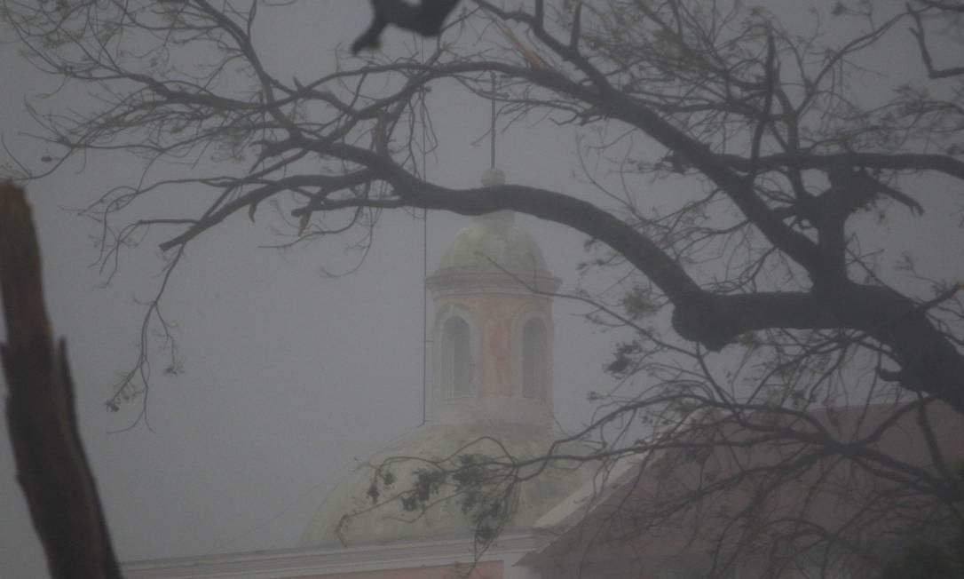 O topo de uma igreja é vista através de galhos durante a passagem do furacão Marina em Porto Rico. A tempestade ocorre poucos dias depois que a região foi devastada pelo furacão Irma, que foi classificado como uma das tempestades atlânticas mais poderosas registradas e deixou um rastro de destruição em várias ilhas do Caribe Foto: RICARDO ARDUENGO / AFP