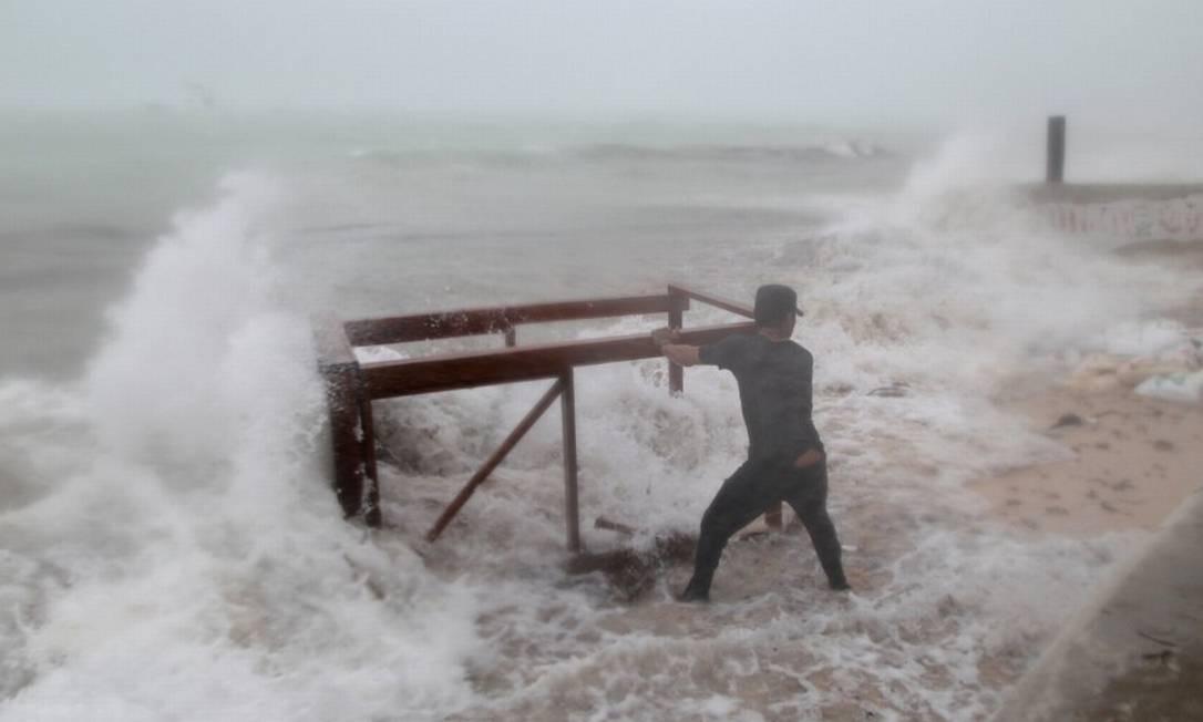 Homem se segura a mesa que pertence ao seu restaurante antes da chegada do Furacão Maria em Punta Cana, na República Dominicana Foto: RICARDO ROJAS / REUTERS
