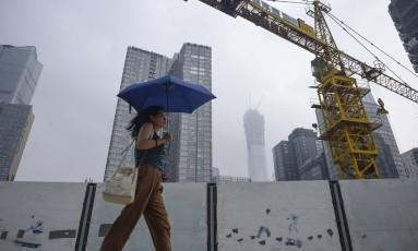 Mulher passa perto de construção em Pequim. Foto: Wang Zhao/AFP