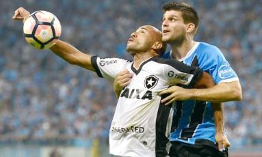 O atacante Roger é marcado pelo zagueiro Kannemann Foto: Dudu Contursi/Raw Image/Agência O Globo