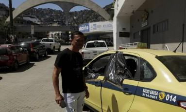 Motorista auxiliar, Flábio Nascimento Souza observa o táxi atingido por 38 tiros na guerra da Rocinha Foto: Gabriel de Paiva / Agência O Globo
