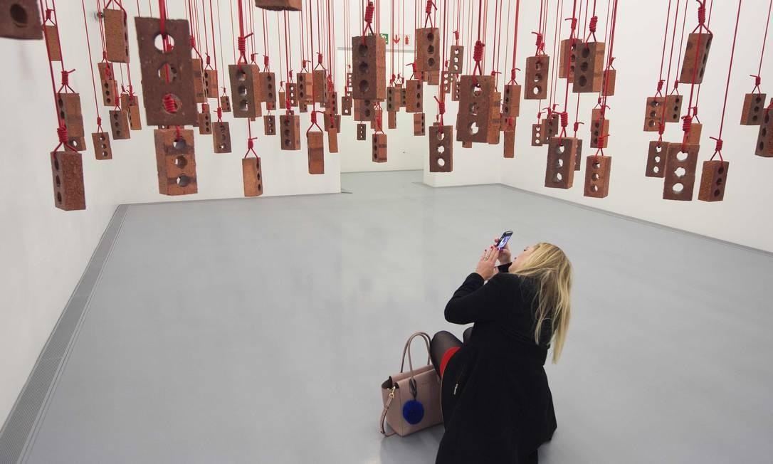 Instalação do artista sul-africano Kendell Geers chama atenção de visitante na abertura do Zeitz Museum of Contemporary African Art em Cape Town Foto: RODGER BOSCH / AFP