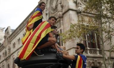 Resistência. Vestidos com a bandeira separatista catalã, jovens participam de protesto em frente a tribunal de Justiça em Barcelona Foto: JON NAZCA/REUTERS