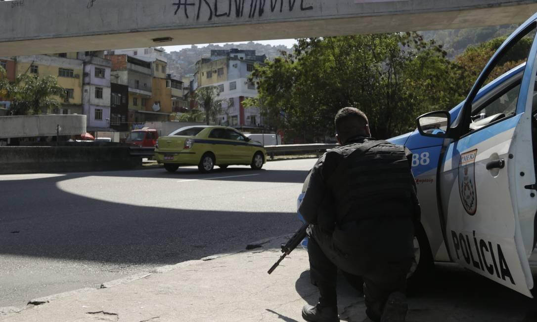 Guarda se protege atrás de carro durante tiroteio na Autoestrada Lagoa-Barra Foto: Gabriel Paiva / Agência O Globo
