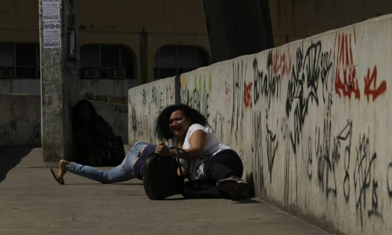 Mulheres se abrigam de tiroteio em passarela Foto: Gabriel Paiva / Gabriel Paiva