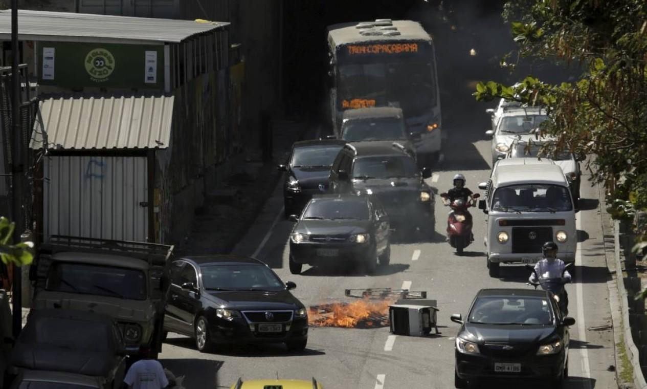 Traficantes jogam objetos com fogo na saída do túnel Zuzu Angel. Logo depois o tráfego foi fechado Foto: Gabriel Paiva / O Globo