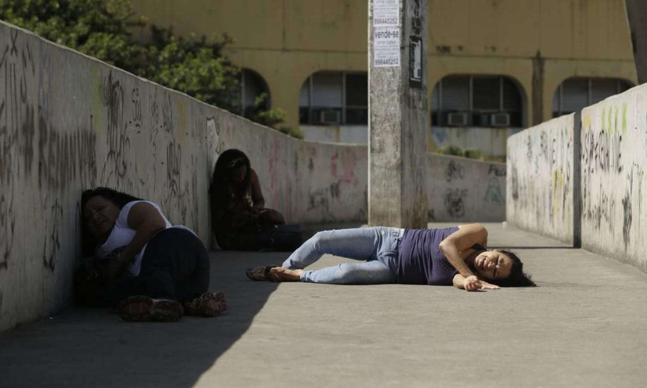Mulher chora enquanto tenta se proteger dos tiros em baixo da passarela da Rocinha Foto: Gabriel Paiva / O Globo