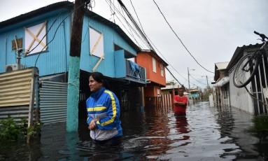 Pessoas caminham em uma rua inundada em Juana Matos, Porto Rico Foto: HECTOR RETAMAL / AFP