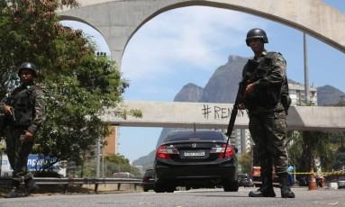 Soldados observam o movimento na Autoestrada Lagoa-Barra, principal acesso da Rocinha Foto: Custódio Coimbra / Agência O Globo