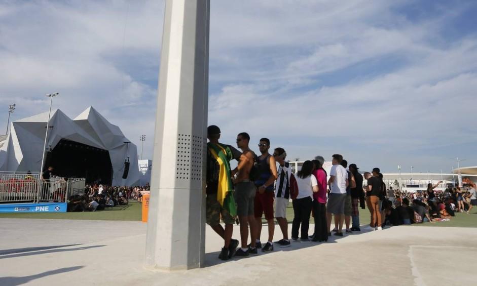 Público aproveita a sombra do poste para se proteger do sol Foto: Roberto Moreyra / Agência O Globo