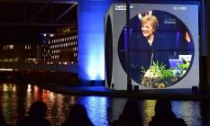 Vitória projetada. Visitantes observam a imagem de Merkel durante o espetáculo no Parlamento alemão sobre a história da instituição. Eleição pode dar 4º mandato à chanceler Foto: TOBIAS SCHWARZ / AFP