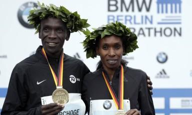 Os compatriotas Eliud Kipchoge e Gladys Cherono posam com as medalhas Foto: Michael Sohn / AP