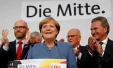 A líder dos conservadores da União Democrata Cristã (CDU) Angela Merkel a correligionários comemoram a vitória, ofuscada pela volta da extrema-direita ao Parlamento do país Foto: REUTERS/KAI PFAFFENBACH