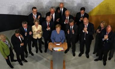 Merkel e partidários durante o discurso da vitória após divulgação de resultados de pesquisas de boca de urna Foto: AP/Pawel Kopczynski
