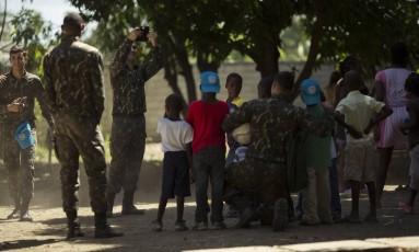 Prestes a deixar o Haiti, militares brasileiros tiram fotos com crianças da Escola Sagrado Coracao de Jesus, em Porto Principe. Foto: Daniel Marenco / Agência O Globo