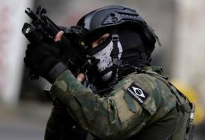 Fuzileiro naval, do grupo Comandos Anfíbios, com buff de caveira, durante operação na Rocinha Foto: Bruno Kelly / Reuters