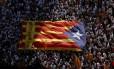 Apoiadores da independência da Catalunha seguram uma bandeira gigante durante um protesto em Barcelona Foto: ALBERT GEA / REUTERS