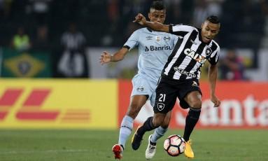 Arnaldo protege a bola da marcação de Léo Moura, do Grêmio: lateral está em alta no Botafogo Foto: Vitor Silva/SSPress
