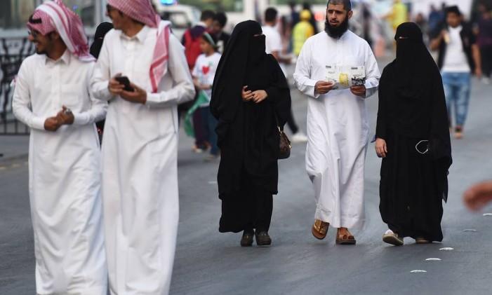 Pessoas andam pela rua Tahlia, em Riad, capital saudita, durante as celebrações do aniversário da fundação do reino Foto: FAYEZ NURELDINE / AFP