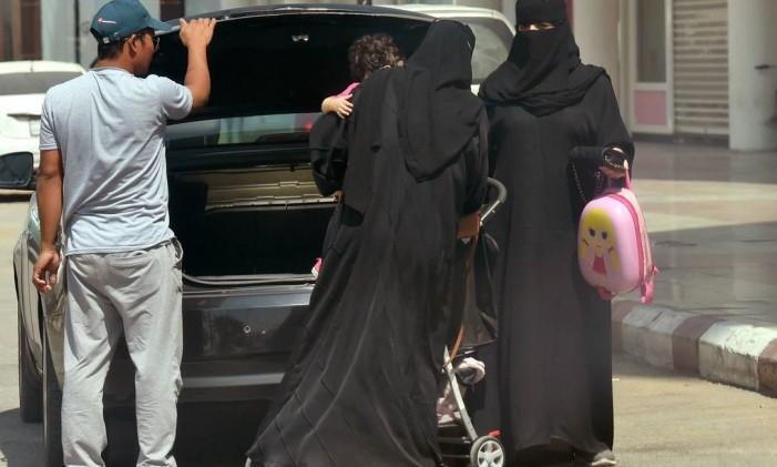 Mulheres sauditas carregam uma criança e seus pertences ao sair de um carro em Riad Foto: FAYEZ NURELDINE / AFP