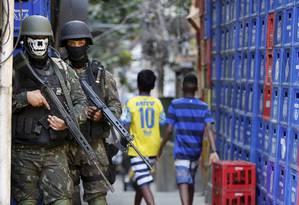 Soldados do Exército com máscaras na Rocinha Foto: Domingos Peixoto / Agência O Globo