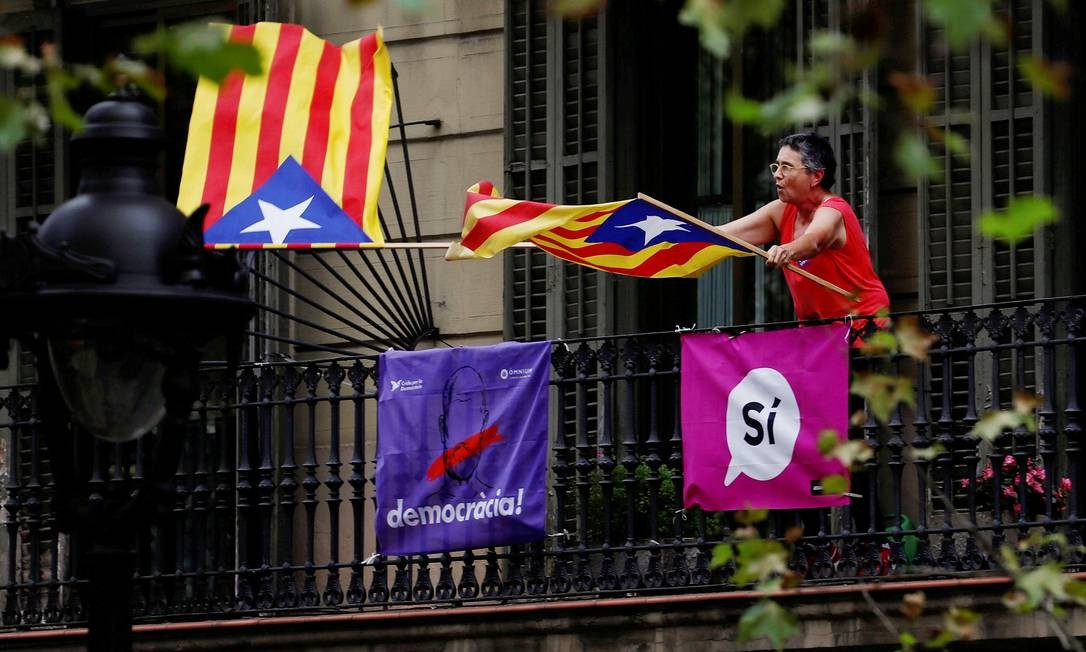 Mulher sacode bandeiras em sinal de apoio à separação catalã; identidade secular e crise econômica aumentam sentimento nacionalista Foto: JUAN MEDINA / REUTERS