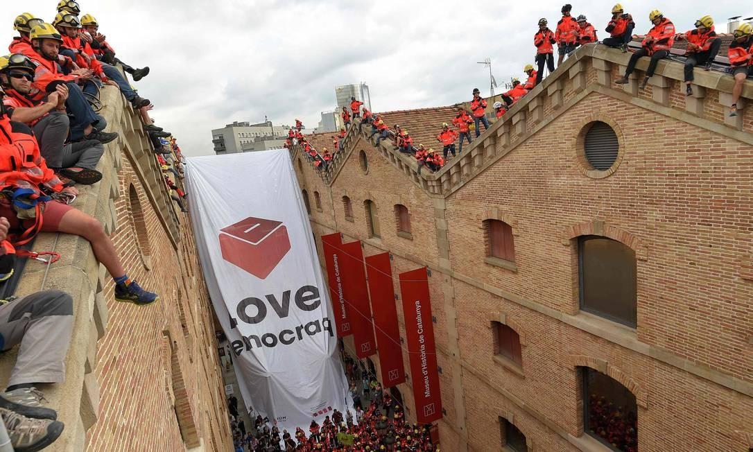 """Até os bombeiros se juntaram aos protestos, com cartazes em que se lê """"Ame a democracia""""; Madri tenta sufocar consulta popular com operações policiais, proibição de sites que promovem votação e detenção de dirigentes favoráveis ao referendo Foto: LLUIS GENE / AFP"""