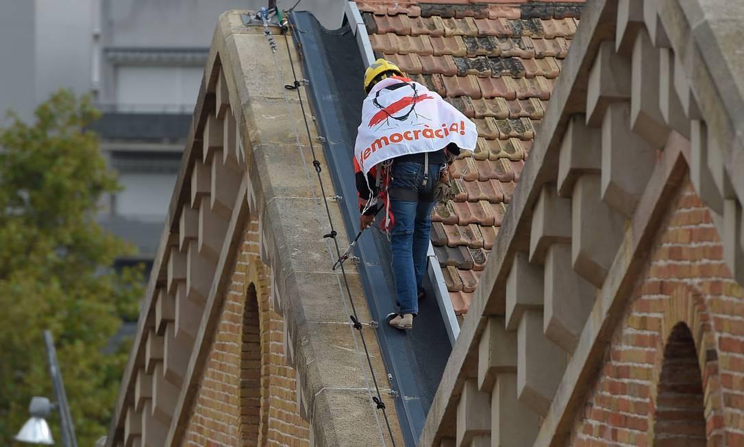 """Bombeiro trabalha com faixa que diz """"Democracia"""" em telhado perto do Museu de História da Catalunha em Barcelona Foto: LLUIS GENE / AFP"""