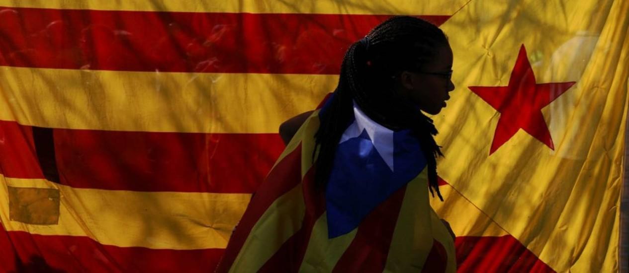 Dia decisivo. Manifestante caminha envolta em bandeira separatista catalã: região desafiou governo espanhol Foto: SUSANA VERA / REUTERS