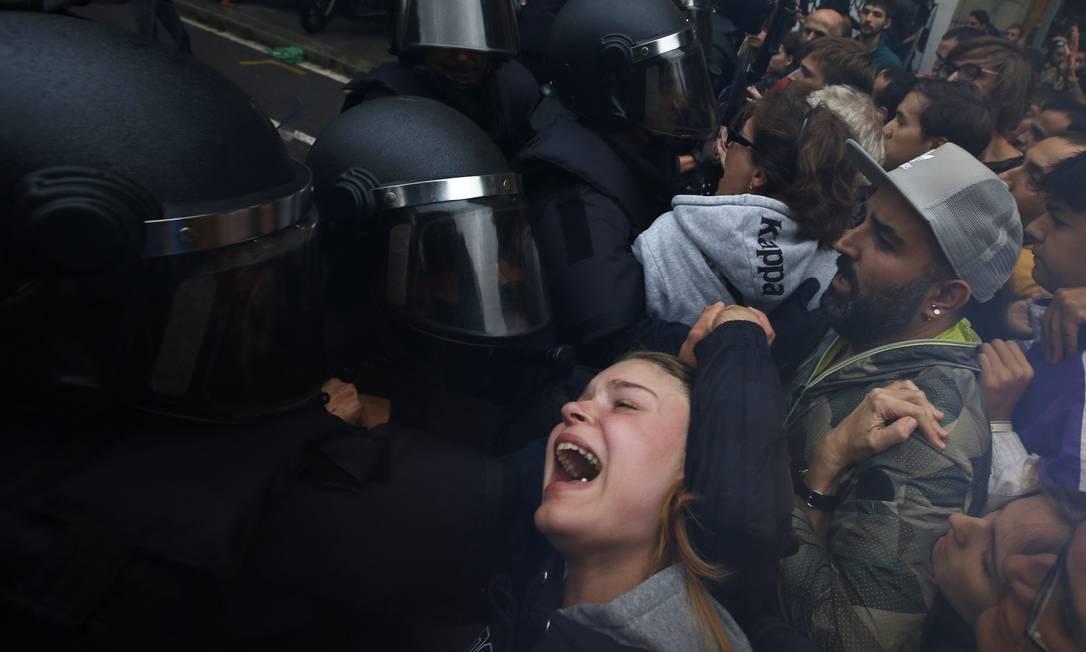 Os confrontos entre policiais e manifestantes nos colégios eleitorais que recebem o referendo de independência da Catalunha já deixaram centenas de feridos Foto: Emilio Morenatti / AP