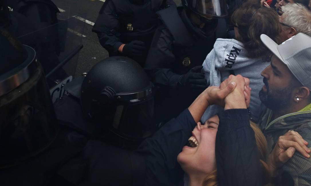 Mulher é empurrada por policiais durante um dos embates em Bracelona Foto: Emilio Morenatti / AP