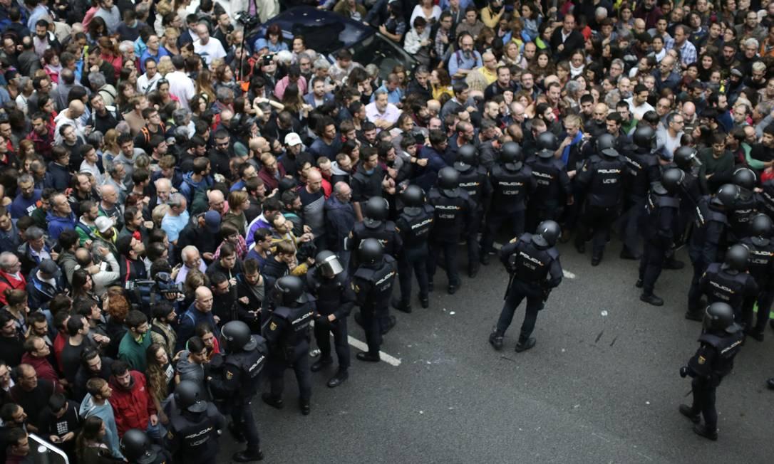 Público faz pressão diante de cordão de isolamento feito por policiais Foto: Emilio Morenatti / AP