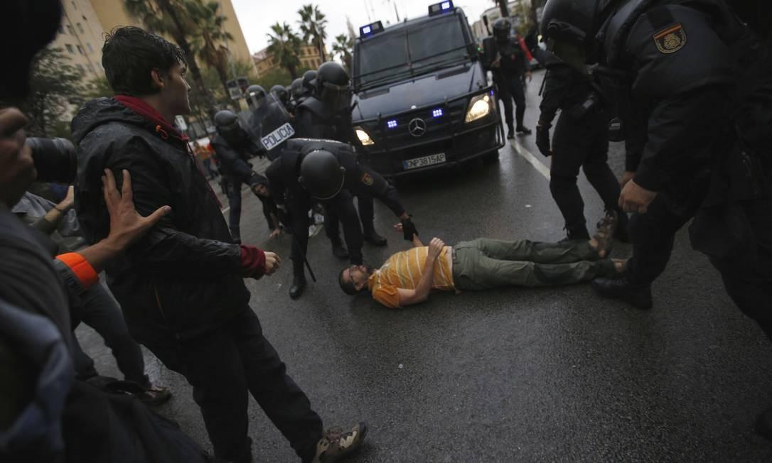 Este homem tentou impedir a passagem de um veículo policial ao se deitar no chão Foto: Emilio Morenatti / AP