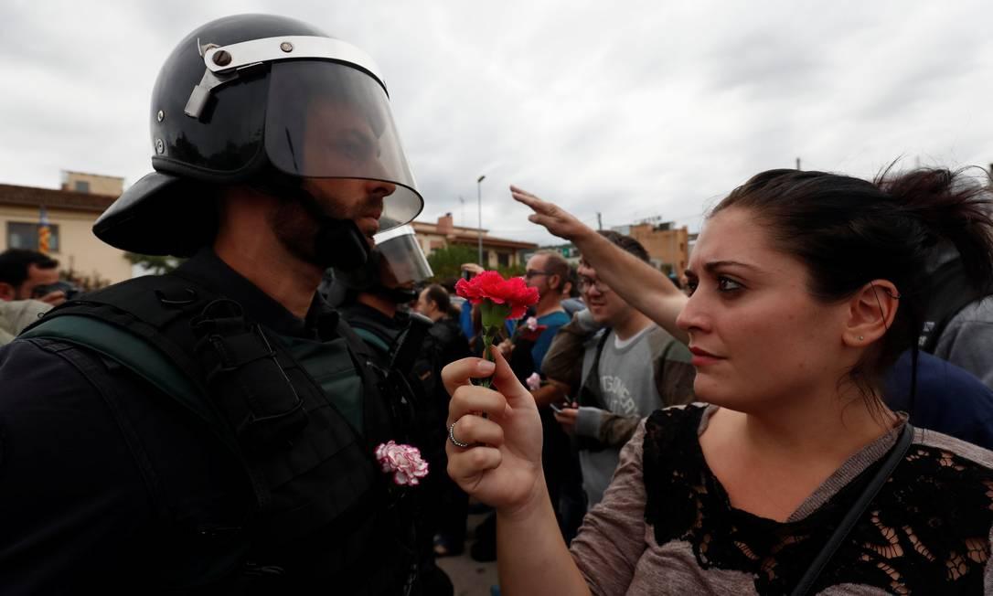 Em protesto contra a truculência, mulher oferece uma flor a um policial Foto: JUAN MEDINA / REUTERS